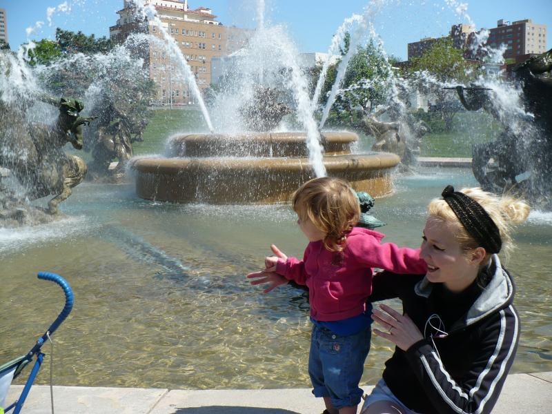 Mother and daughter playing in front of the J.C. Nichols Memorial Fountain. The fountain is one of the most recognizable and popular waterworks in Kansas City.