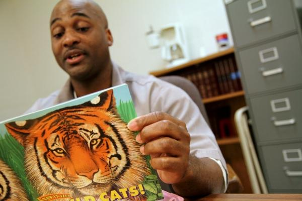 Missouri inmate Callion Barnes reads a storybook about tigers.