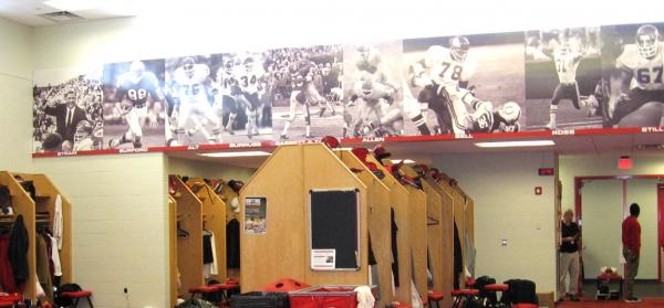 Scenes of KC Chiefs' great moments hover over somber locker room as Romeo Crennel is fired as coach.