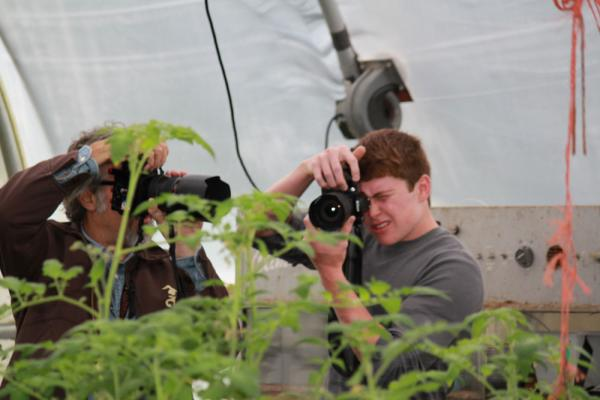 Lexicon of Sustainability founder Douglas Gayeton photographs Ames High sophomore Will Weber photographing a high tunnel at Berry Patch Farm in Nevada, Iowa.