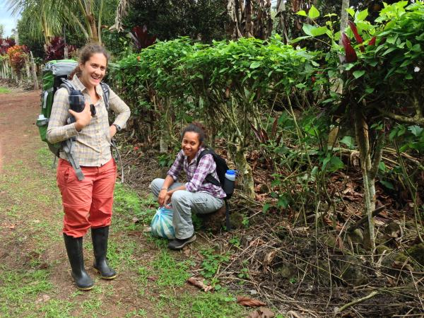 Maricruz Jaramillo (standing) and Samoa Asigau wait for their ride back to the Charles Darwin Research Station after an early morning of catching birds in an agricultural area on Santa Cruz Island.