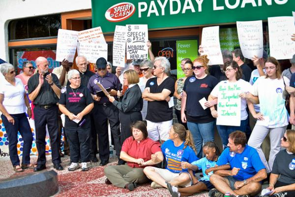 Supporters of the ballot initiative to cap the annual rate of loans at 36 percent rally at the entrance of a Kansas City payday lender in September 2012.