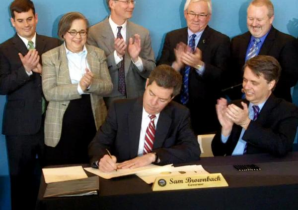 Dignitaries applaud as Governor Sam Brownback signs a bill lowering employers' unemloyment insurance costs.