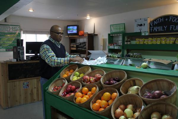 Terry Glenn re-stocks shelves at the Harvest Learning Center Market. The store is in the basement of the church where Glenn is pastor.