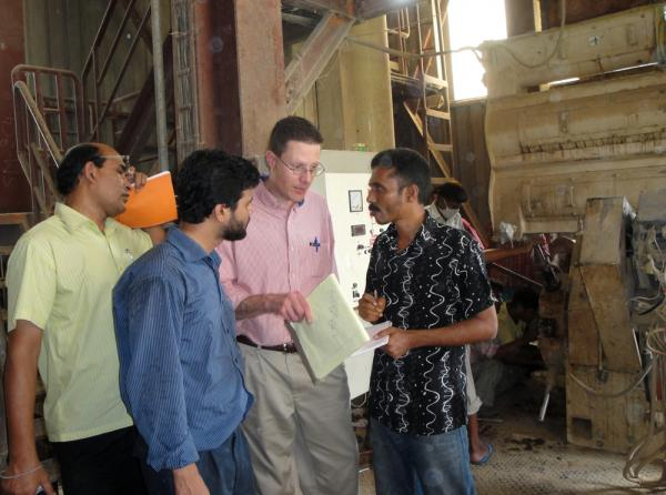 Kurt Rosentrater, center, and Mamun Ur Rashid, in blue shirt, meet with workers at a feed mill in Bangladesh as part of a project designed to improve fish feed in the developing world.