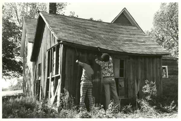 Two men deconstruct a former slave cabin in Trenton, Mo., in 1977 before relocating it to the Black Archives of Mid-America. The reconstructed cabin is still on display at the Black Archives, located at 1722 E. 17th Terrace.