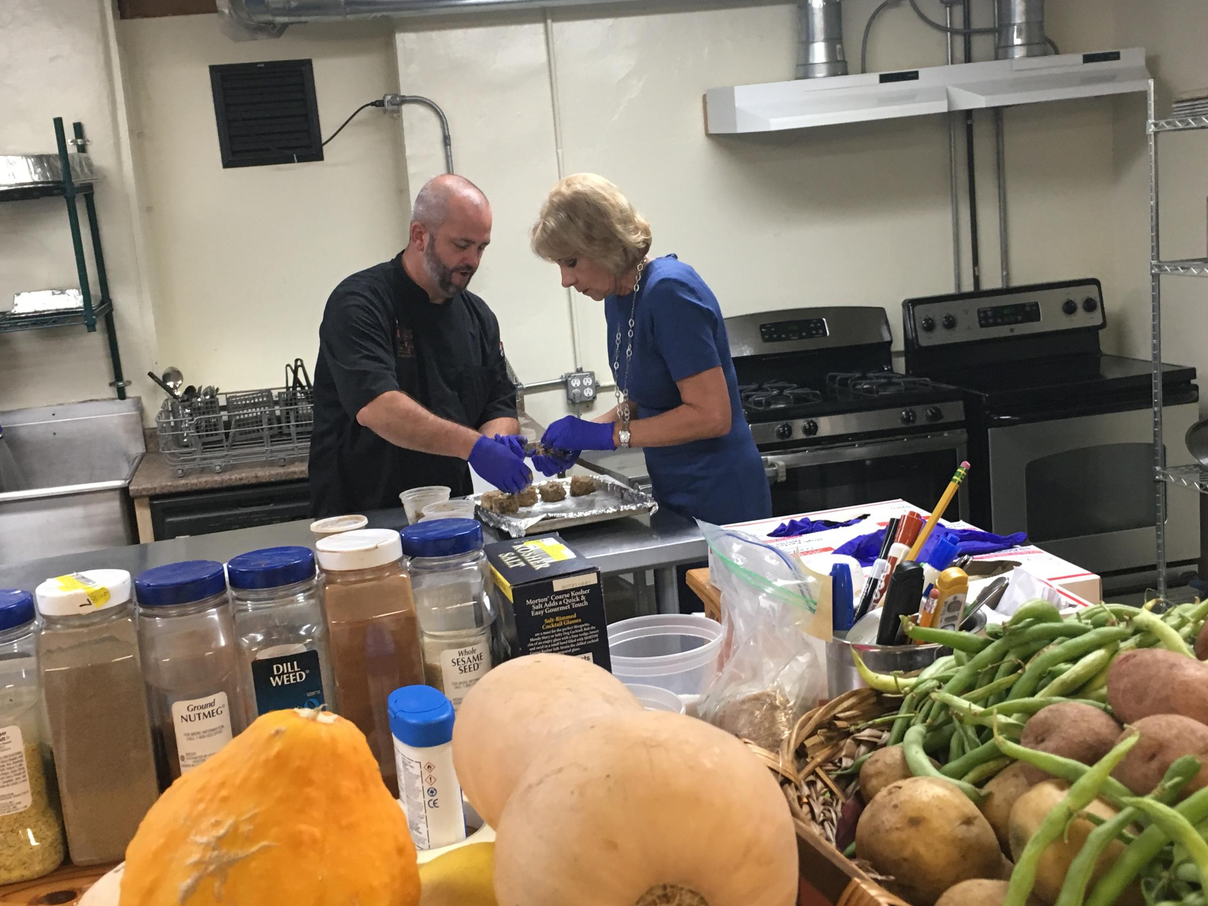 Kansas City Academy Chef Mark Zukaitis teaches U.S. Secretary of Education Betsy De Vos to make veggie burgers. The school makes theirs with leftover rice and beans from the previous day's lunch