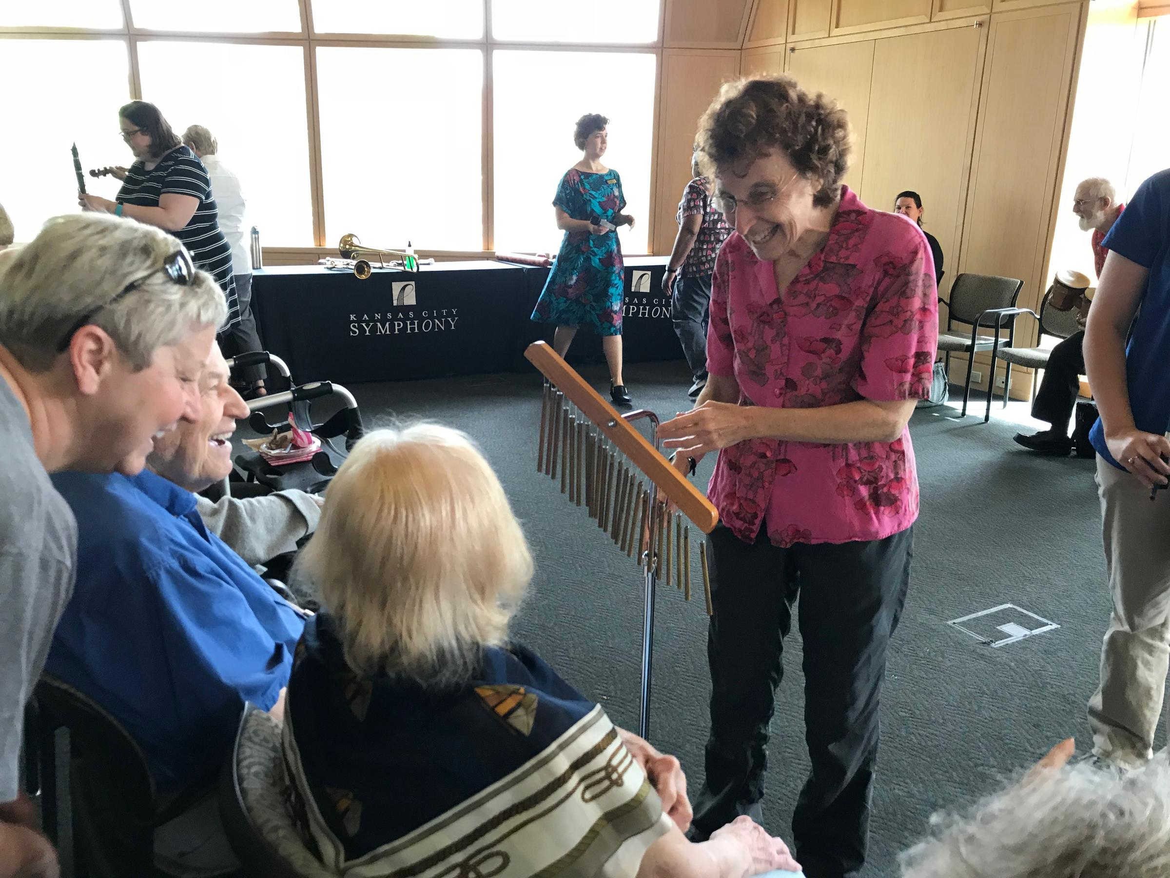 Memory Cafe co-organizer Deborah Shouse demonstrated the chimes to participants during the group's May gathering. CREDIT ANNE KNIGGENDORF / KCUR 89.3