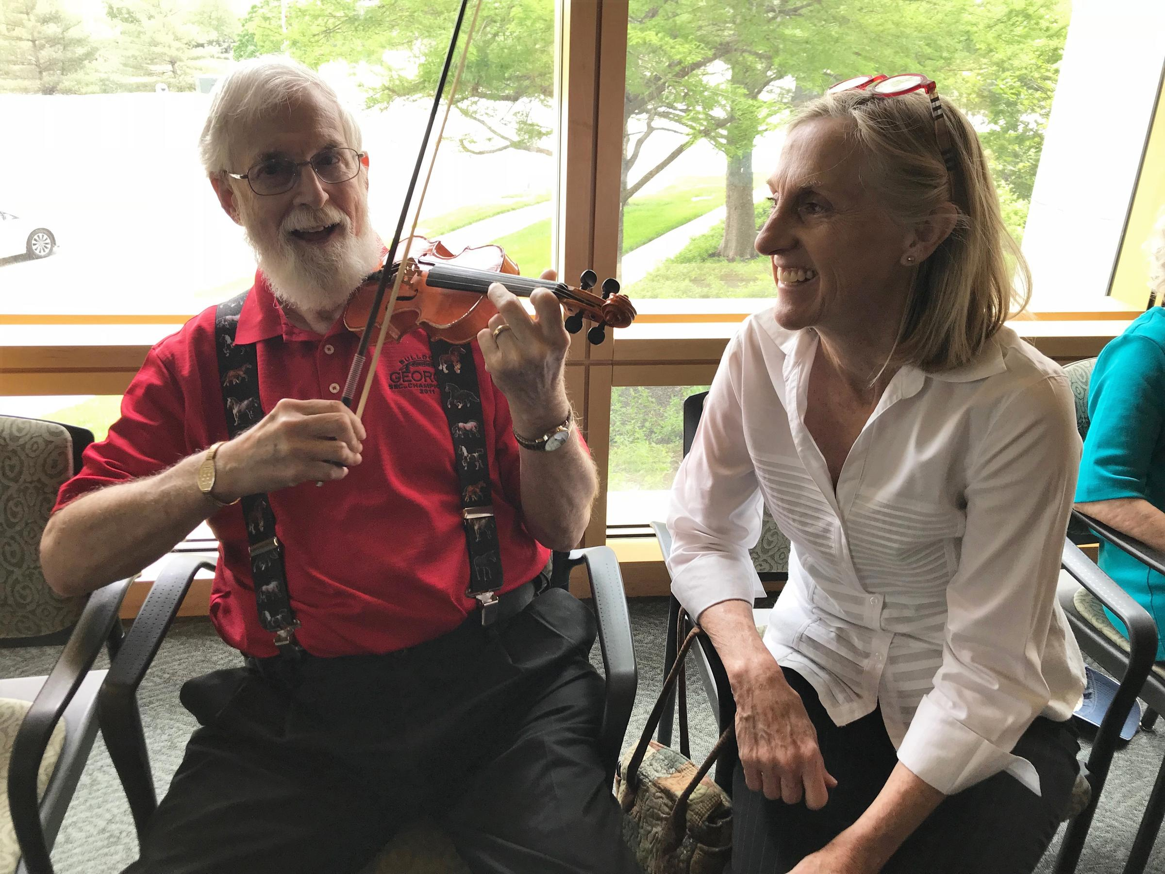 Dennis McCurdy tried out a tiny violin during the May meeting of Memory Cafe, which featured a special guest from the Kansas City Symphony. Deb Campbell, co-founder of the group's local chapter, looked on. ANNE KNIGGENDORF