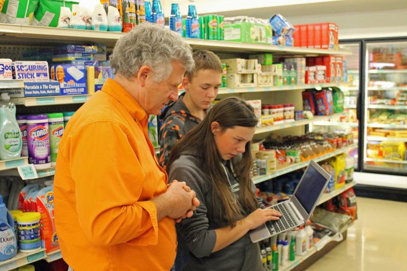 Cody-Kilgore Superintendant Todd Chessmore helps students check inventory at the store.