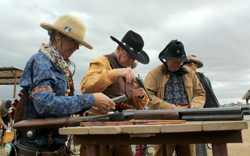 Members of the Single Action Shooting Society load their rifles and pistols at the Iron Hero match, including Dannette Ray of Boulder, Colorado (left), aka Marie Laveau.