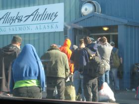 Fishermen, processing workers and others battle the bugs as they wait for a flight Monday in King Salmon.