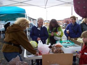 Shoppers at the Warehouse Mountain Farms table at an October farmer's market in Dillingham.