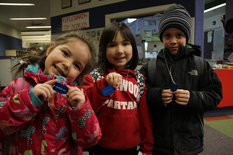 First graders Ann Tucker, Izabelle Savo, and Travis Wassillie earned their dog tags by reading 500 minutes.