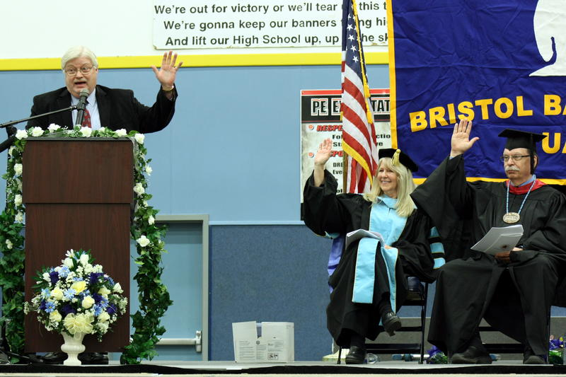 Robert Gillam poses a question during his commencement address; BBC Director Dr. Deborah McLean and UAF Chancellor Brian Rogers react.