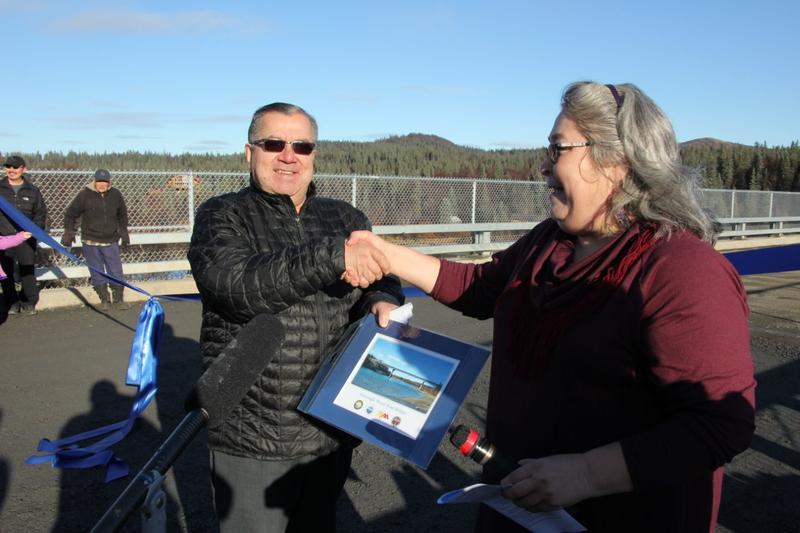 Aleknagik City Administrator Kay Andrews presents Senator Lyman Hoffman with a photo of the bridge.