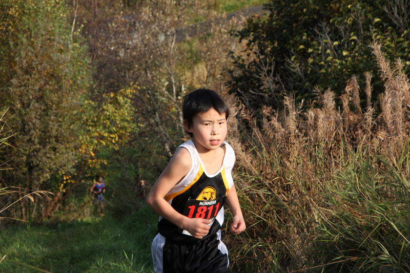 A young runner from New Stuyahok gutting out a steep climb in Dillingham.