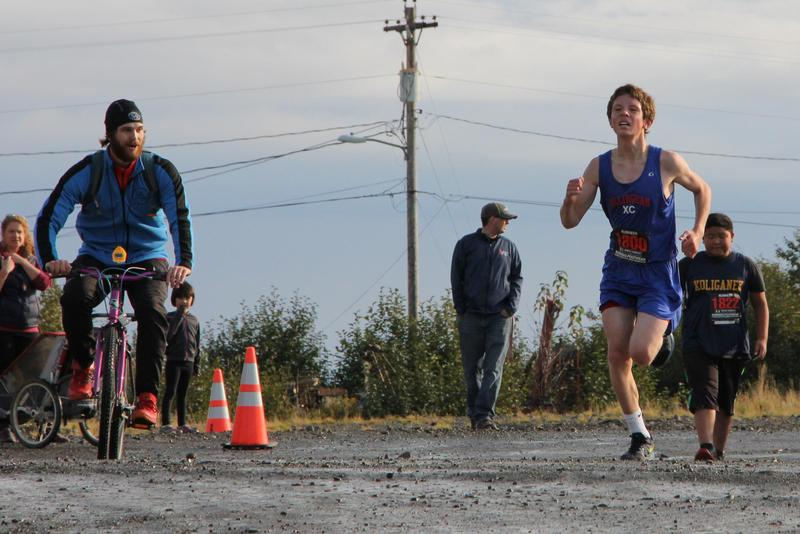 Sam Calvert runs for a first place finish with coach Andrew Slagle adding some motivation.