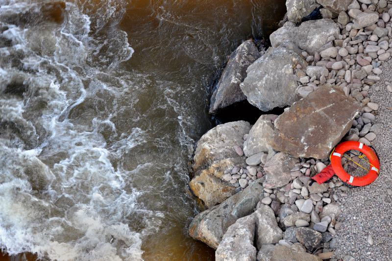 An orange lifebuoy rests next to the Colorado River underneath the Grand Avenue Bridge.