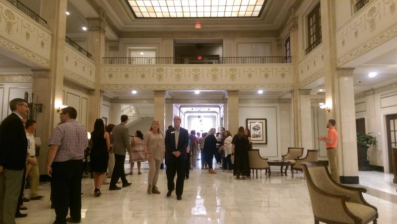 The grand hotel lobby features marble floors and pillars.