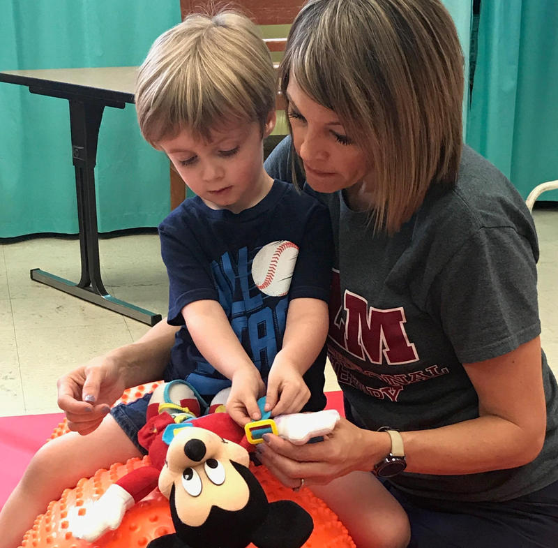 A young patient receives hands-on care from a clinic volunteer.
