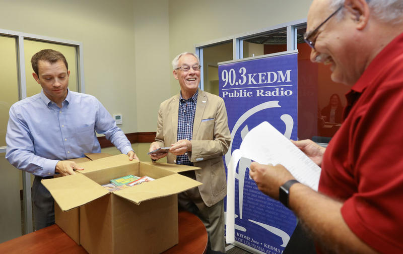 Freeman Stamper (center) unpacks the CD collection with KEDM's Jay Curtis and Mark Henderson