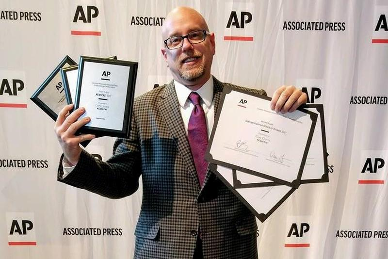 News Director Cory Crowe proudly shows off the numerous awards won by KEDM at the Associated Press Louisiana-Mississippi News Excellence Awards.