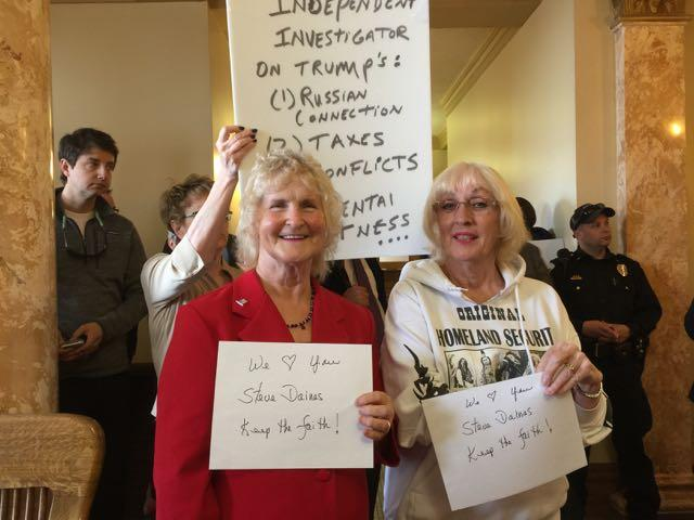Sisters Fee Lamping, L, and Carol Dean, R, hold signs in support of Daines