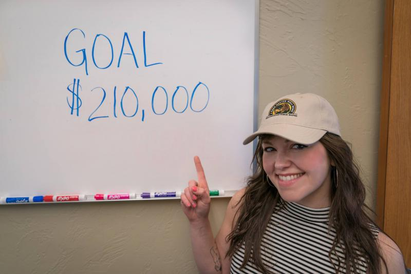 YPR's Brie Ripley posing with our surprassed goal of $210,000!