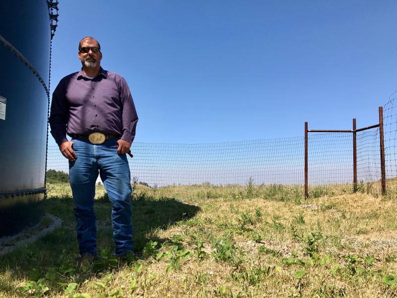 Dustin White, the Chippewa-Cree tribal water director, stands next to a water storage supply tank on the Rocky Boy's reservation.