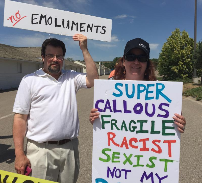 Laura Wight stands with her sign in the designated protest area