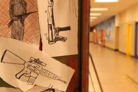 The inside of a locker containing drawings of guns (re-enactment).