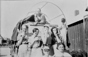 When Harry Forester lost his farm to the dust and Depression in Oklahoma, the family converted its truck into a modern-day covered wagon and migrated to California in 1936, where Forester had found work. Two of his daughters (Louise, front row, left, in cap; and Shirley, second row, second from right) help tell the story of their father's broken dreams and the journey to a new life.