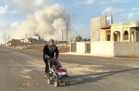 Moments after a deadly air strike hits the Sunni village of Al Barra, a Syrian woman pushes her stroller away from the blast.