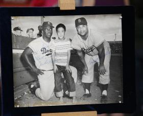 At ANTIQUES ROADSHOW in Palm Springs, California, a guest brings in this 1956 signed photo of himself at ten years-old, posed between baseball Hall of Famers Jackie Robinson (left) and Roy Campanella (right)- pioneers in breaking the color barrier in Major League Baseball. Its estimated worth is $6,000 to $8,000.
