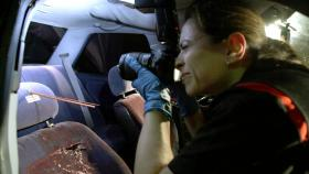 Joanna Grivetti, crime scene investigator in the homicide division of the Richmond, California, police department, inspects a vehicle in which a young man was shot in the back of the head during a drive-by shooting on March 9, 2012.