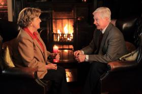 Alan (DEREK JACOBI) and Celia sit by the fireside in a café, waiting for their families