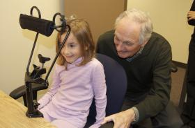 Alan helps a young participant in Dr. Bea Luna's lab. Luna's research shows how adolescents cannot perform certain attention tasks that come easily to both adults and children.