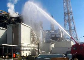 A fire engine douses the spent fuel pool of Reactor 3 at Fukushima Dai-ichi.
