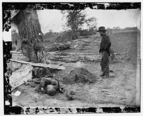 A soldier looking upon a Union soldier's grave with the body of a Confederate soldier seemingly tossed aside in Antietam, Maryland. (September 1862) Courtesy of Library of Congress