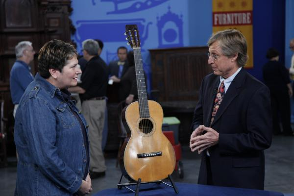"James Baggett (right) appraises an 1899 C. F. Martin guitar that was stumbled upon in a vacant commercial real estate space and is now valued at $4,000 to $5,000 in the ANTIQUES ROADSHOW special ""Finders Keepers."""