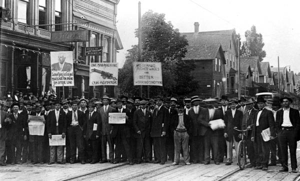 "Picketers during the 1913 strike. One carries a sign, ""One Man Machine - Our Agitator."" Another carries a sign reading ""We Demand Higher Wages and Better Working Conditions."""