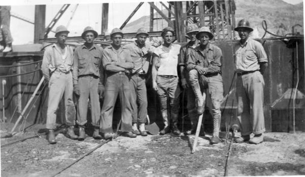 Group of workers lined up on the Grand Coulee Dam construction site with their hardhats on.
