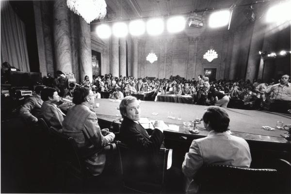 The Dick Cavett Show of 8/1/73 on location from the Senate Watergate Committee hearing room in Washington D.C. Dick Cavett looks over shoulder at camera; flanked by members of the committee with their backs to the camera – left to right: Senator Herman Talmadge, Senator Daniel Inouye, Senator Lowell Weicker, and Senator Howard Baker.