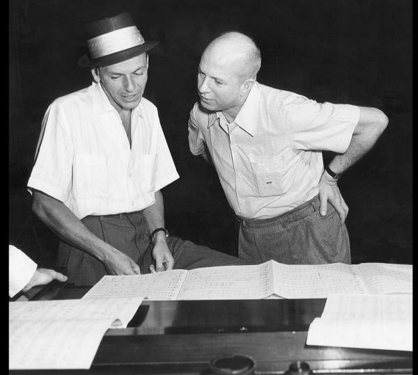 Frank Sinatra (left) and Jimmy Van Heusen looking at music together, 1950s.