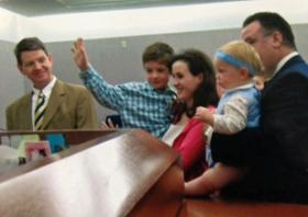 Jerry, 5, raising his hand to take the judge's oath when Abbey was adopted. Mom Susie holds Jerry. Dad Brian Harris, dark suit, holds Abbey. Their attorney looks on.