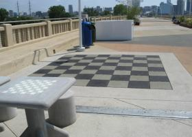 Sit-down chess boards sit next to a human-size board at the Continental Bridge park.