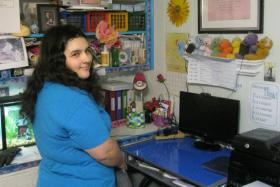 Melissa Richardson, standing by the computer at home where she took classes online. Virtual classes helped Melissa, who's autistic, graduate high school.