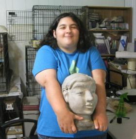 Melissa, a talented artist, holds a ceramic bust of herself that she sculpted. She also likes to write, as does brother William.