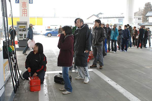 People in Sendai lining up for fuel at an operating gas station.